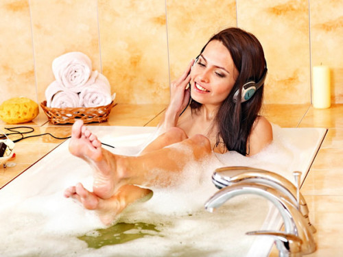 девушка принимает ванну и слушает музыку