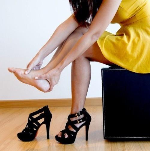 девушка ощупывает ступню ноги