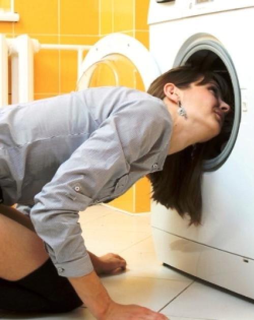 девушка смотрит внутрь стиралки