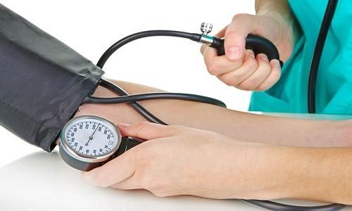 доктор измеряет АД пациенту