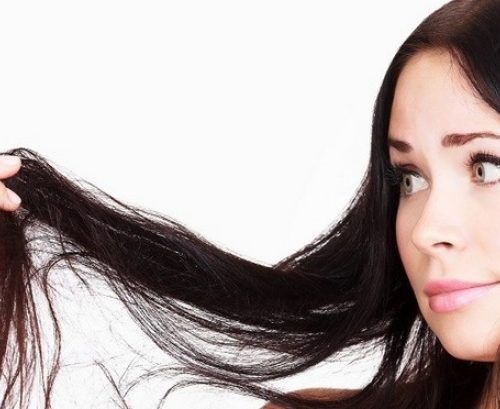 девушка смотрит на кончики волос