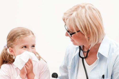 врач оказывает помощь ребенку при кровотечении из носа