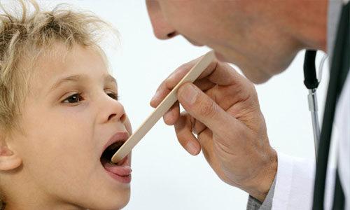 врач смотрит горло у ребенка
