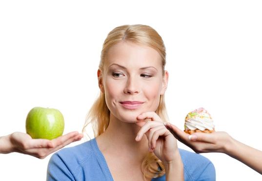 Девушка, выбирающая между яблоком и пирожным