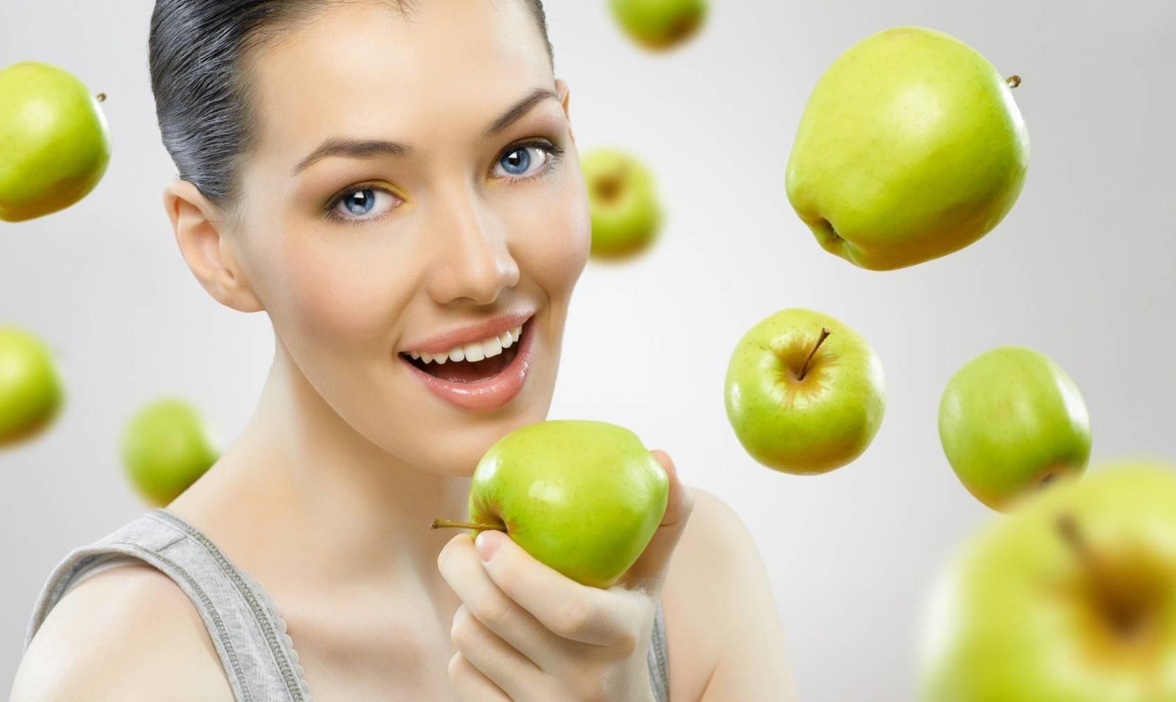 девушка держит яблоко
