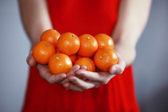 Девушка держит мандарины