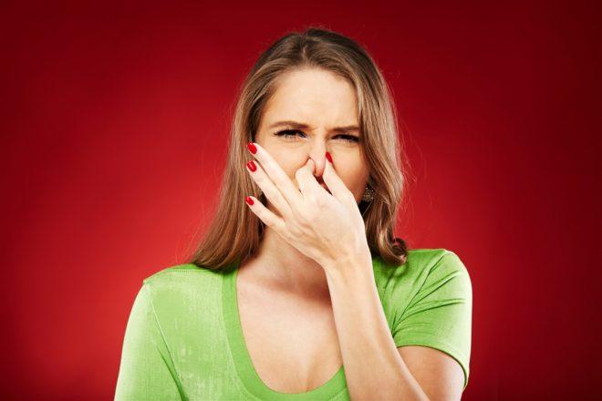 женщина морщится от запаха